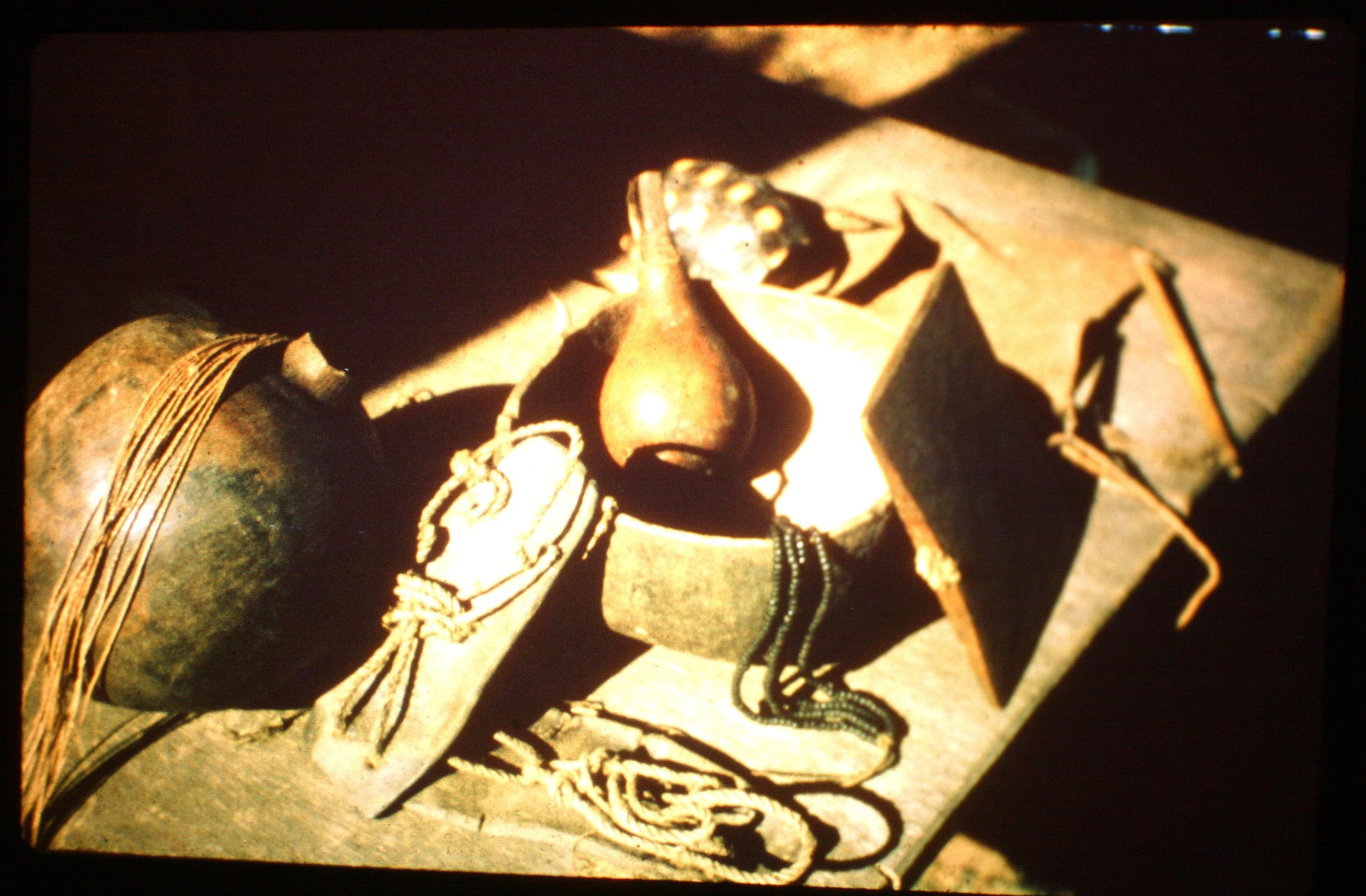 Ayoré artifacts - clay water jug, tapir hide sandals, maraca, gourd bowl, wooden whistle, woman's beads, men's rope