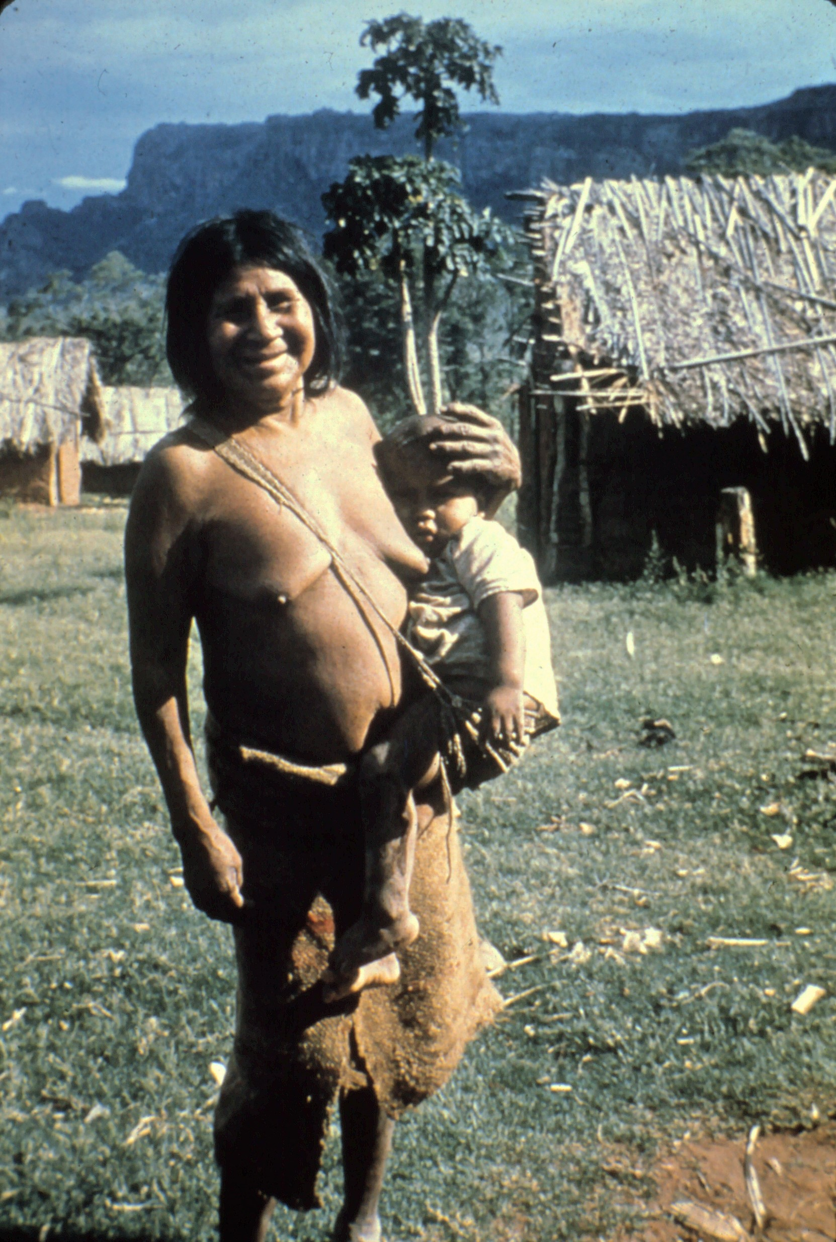 Ayoré woman baby sitting, carrying the infant in it's woven baby sling.