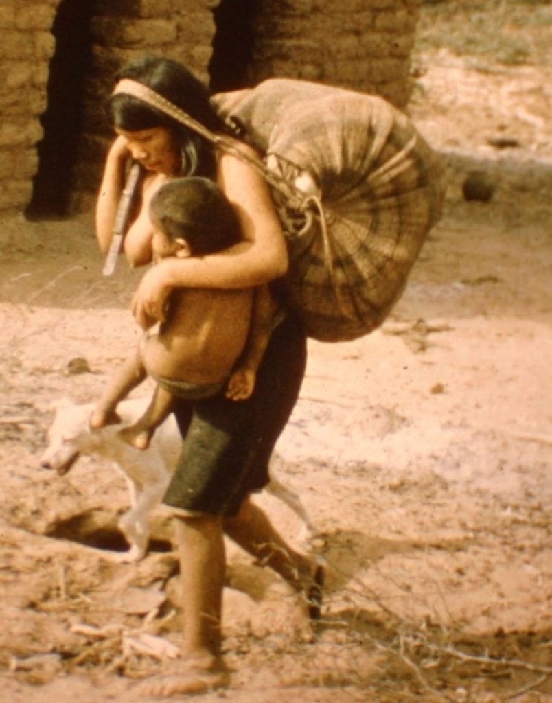 Ayoré woman child in sling, dog at her side, and heavy bag supported by band across her forehead.