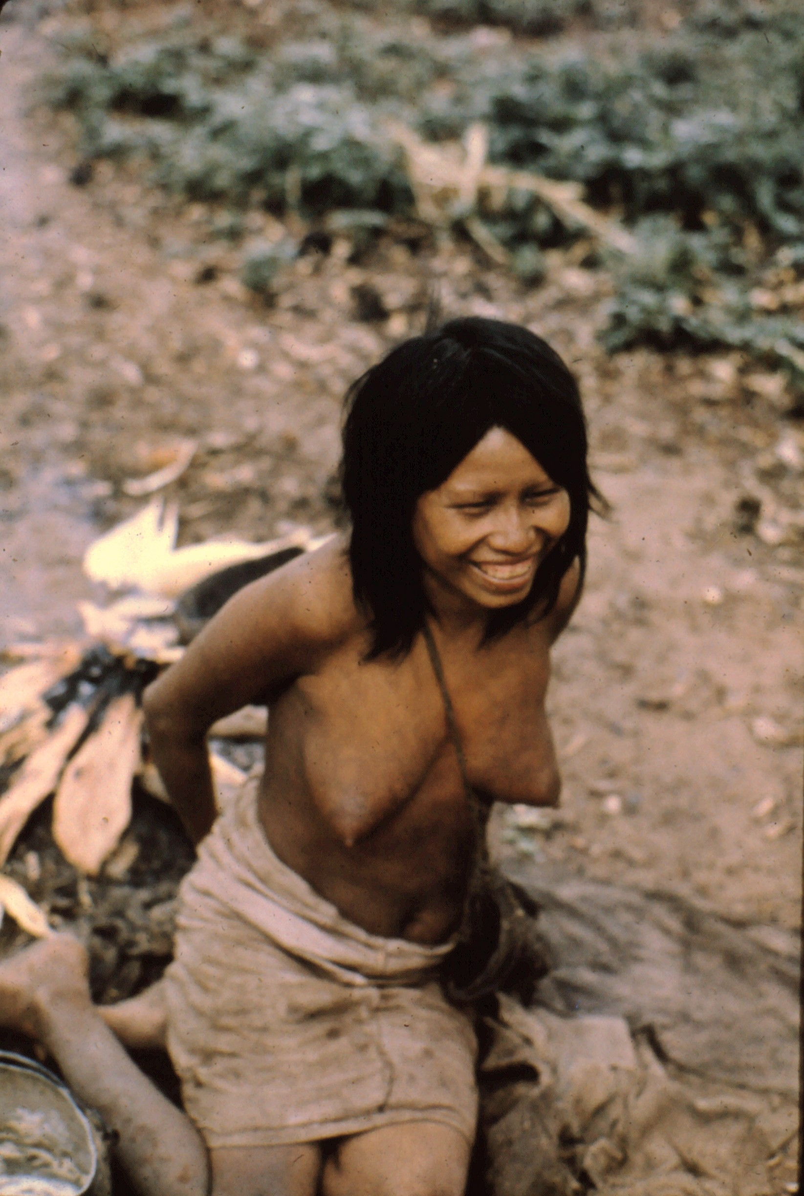 Ayoré woman takes circular bag off her back, but baby sling remains around her shoulder.