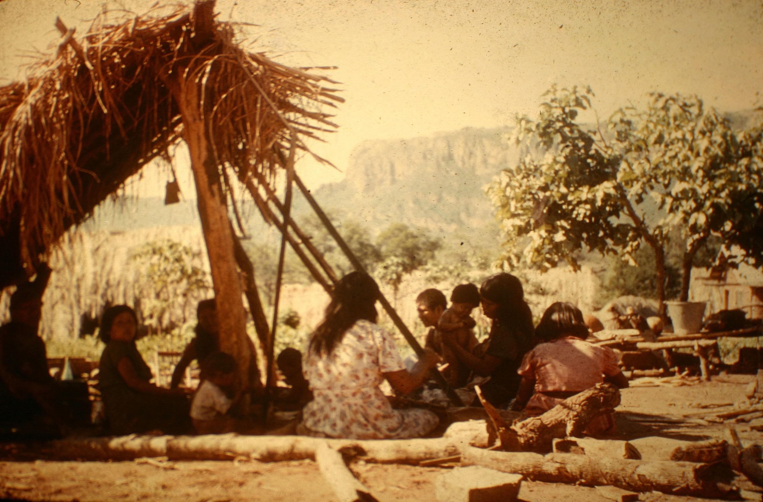 Ayore ladies in lean-to weaving and visiting.
