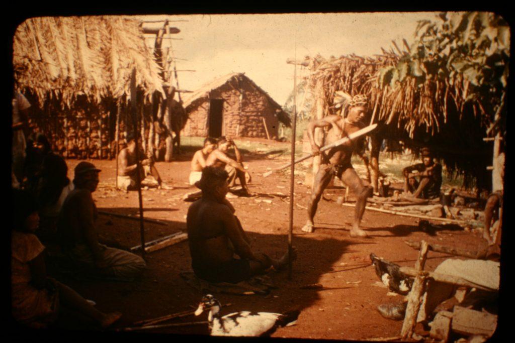 Ayore man performing with jaguar headdress and lance