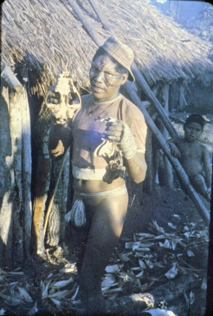 Ayore man with facial marks, feather loin cloth, and treasured artifacts.