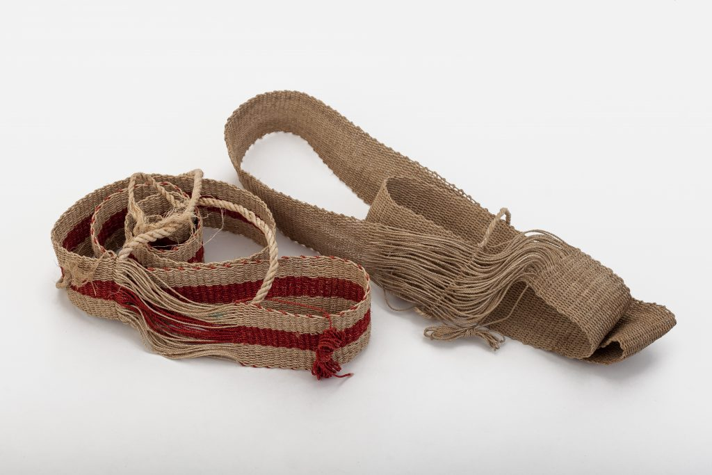 Woven belts or straps used by older men as a back support (wrapped around body, and then about the bended knee.