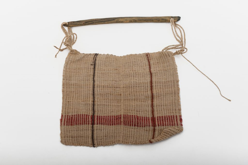 Woman's flyswatter with a stick for a handle; the weave is done with hands, not using a needle, and is called 'docora'.
