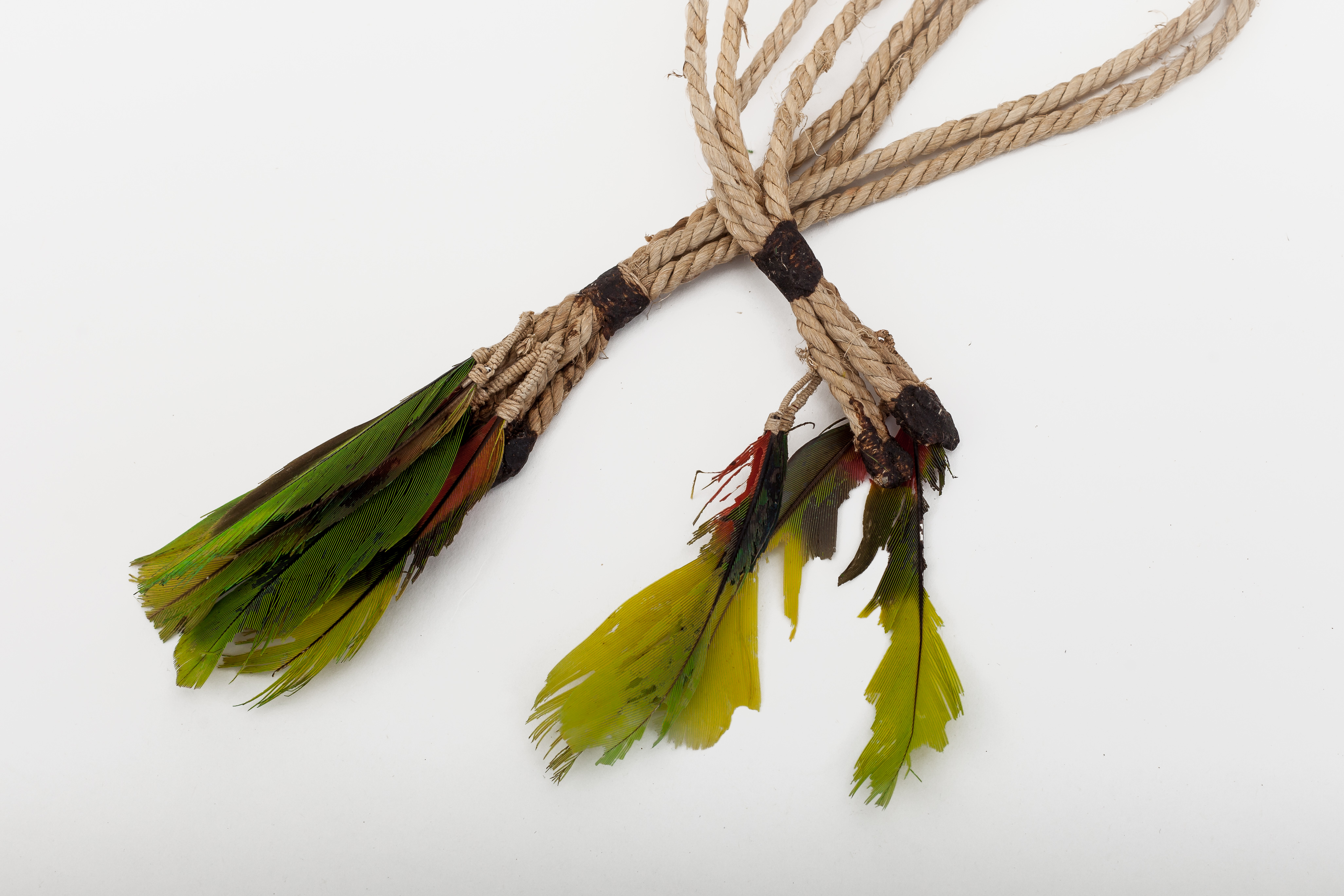 Men's arm adornments also serve to chase away insects. Worn on upper arms of young men with tail feathers of birds on the ends.